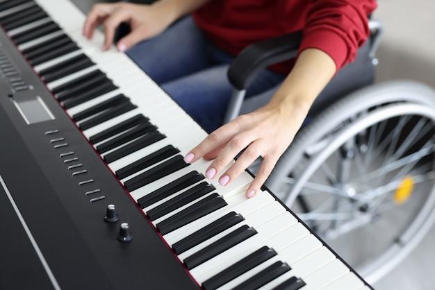 Donna in sedia a rotelle che suona il sintetizzatore mentre fa musica