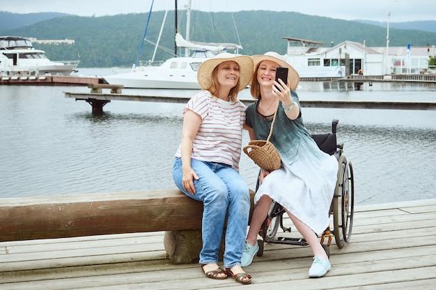 Donna in sedia a rotelle che si fa un selfie con la sua amica sullo sfondo del molo con yacht, catamarani