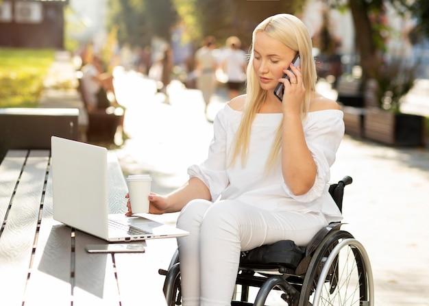 Donna in sedia a rotelle utilizzando laptop all'aperto e parlando al telefono