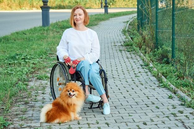 Una donna su una sedia a rotelle cammina con il suo cane all'aperto. giornata internazionale delle persone con disabilità