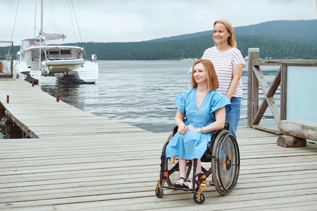 Una donna su una sedia a rotelle cammina con sua sorella o la sua amica su un molo di legno in riva al mare