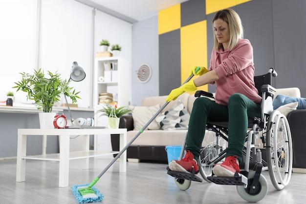Una donna in sedia a rotelle lava il pavimento con la scopa. pulizia interna da parte di persone diversamente abili