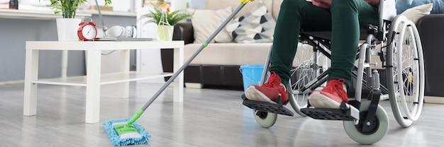Donna in sedia a rotelle lava il pavimento con uno straccio per pulire gli interni da persone con disabilità