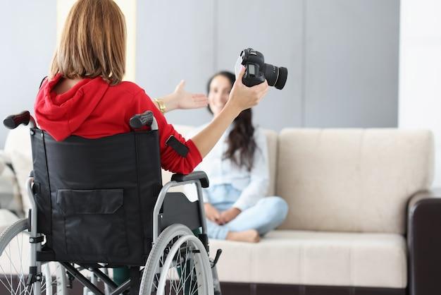 La donna in sedia a rotelle con la macchina fotografica conduce la sessione domestica della foto