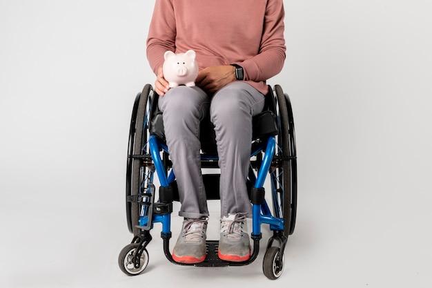 Donna in sedia a rotelle con salvadanaio
