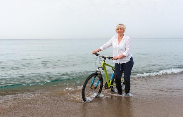 Donna che spinge la sua bicicletta attraverso l'acqua di mare poco profonda sul bordo della spiaggia in una giornata nuvolosa e nuvolosa