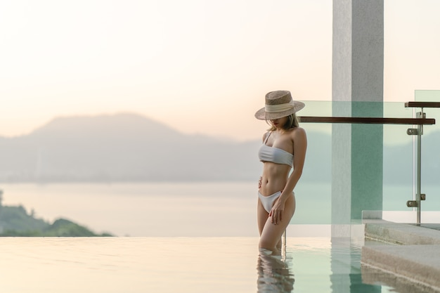 Donna in bikini bianco che cammina posa vicino alla piscina con il balcone in vetro trasparente e vista sull'oceano.