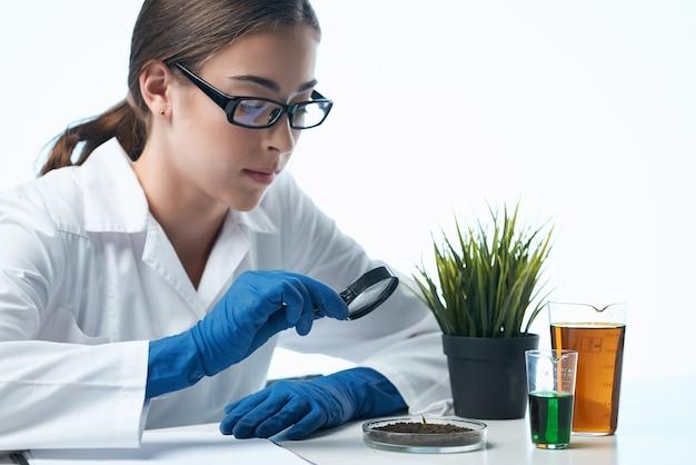 La donna in camice bianco esamina la microbiologia delle piante