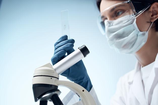 Test professionale del microscopio da laboratorio in camice bianco da donna
