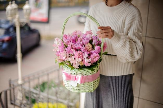 Donna in maglione bianco carino tenendo un bel cesto di vimini verde con fiori rosa