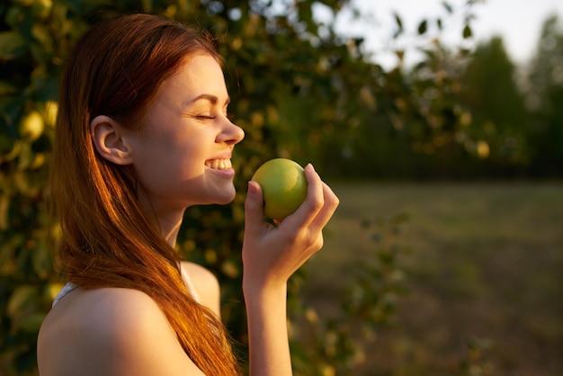 Donna in abito bianco in un campo con mele in mano