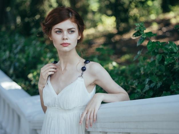 Donna in abito bianco glamour aria fresca foglie verdi a piedi modello