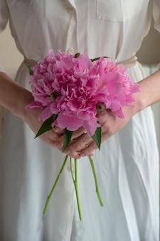 Donna in vestito bianco che tiene i fiori rosa delle peonie dei pioni. avvicinamento