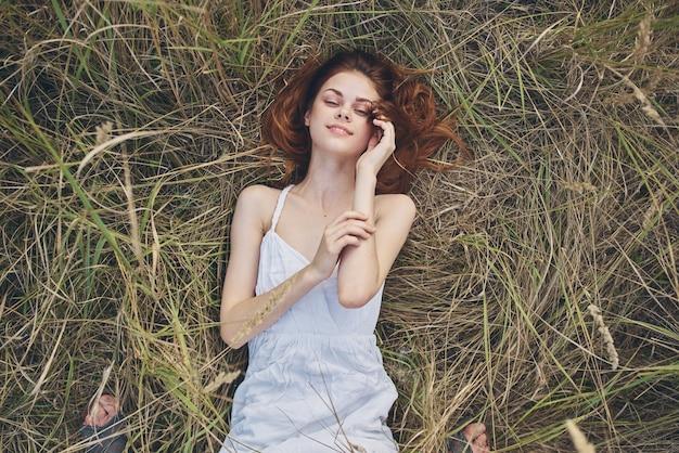 Una donna in abito bianco giace sull'erba con gli occhi chiusi riposando il sole