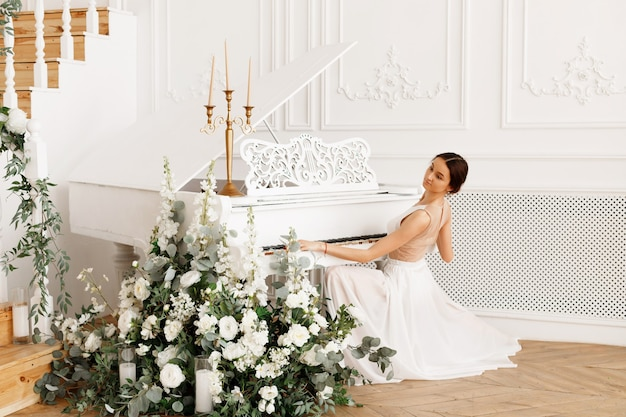 Donna in abito bianco vicino al pianoforte