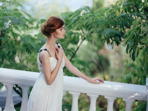 Donna in abito bianco nel lusso del parco in grecia