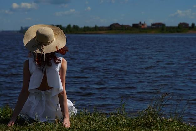 La donna in abito bianco si siede sulla riva del fiume, vista posteriore, acque blu profonde sullo sfondo. copyspace