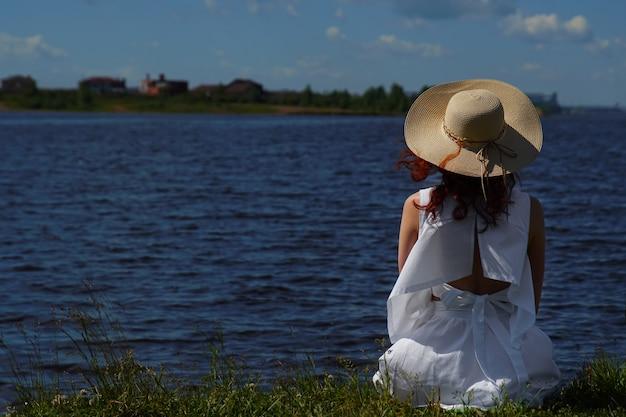 La donna in abito bianco si siede sulla riva del fiume, vista posteriore