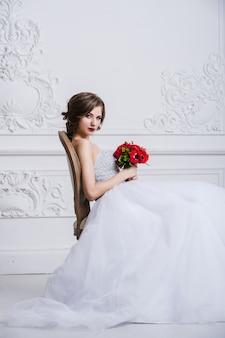 Donna in abito bianco seduto sulla sedia d'epoca antica. guardando la fotocamera e sorridente. rovesciato con fiori tra le mani.