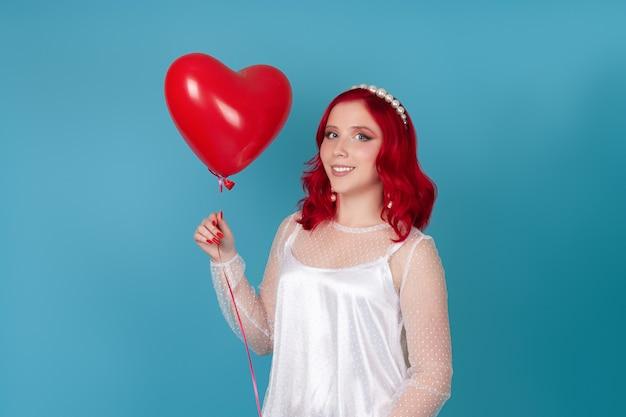 Donna in un abito bianco con i capelli rossi tiene in mano un palloncino volante a forma di cuore