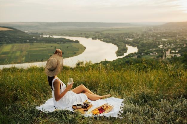 Donna in abito bianco con cappello di paglia con bicchiere di vino, lamponi, croissant, formaggio brie, ciliegia, albicocche su manto bianco.