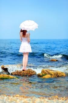Donna in abito bianco con ombrellone su una spiaggia