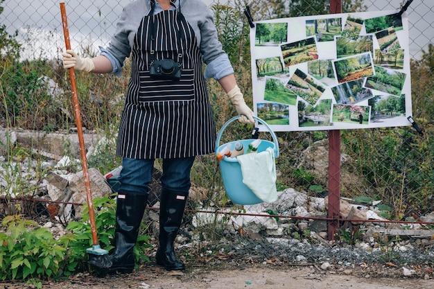 Donna in guanti bianchi con prodotti per la pulizia vicino alla discarica di rifiuti. dice no all'inquinamento ambientale. parcheggi poster invece di discariche su una recinzione a catena