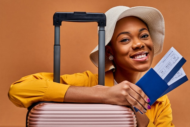 Una donna con un cappello bianco e una giacca gialla, appoggiata a una valigia, tiene in mano un passaporto blu con due biglietti. concetto di viaggio
