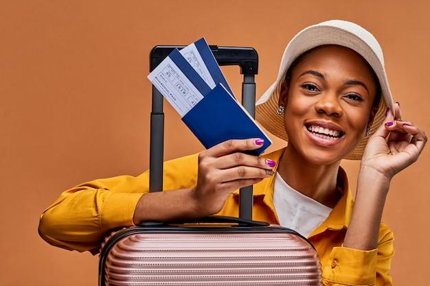 Una donna con un cappello bianco e una giacca gialla si appoggia a una valigia mostra un passaporto blu e due biglietti. concetto di viaggio