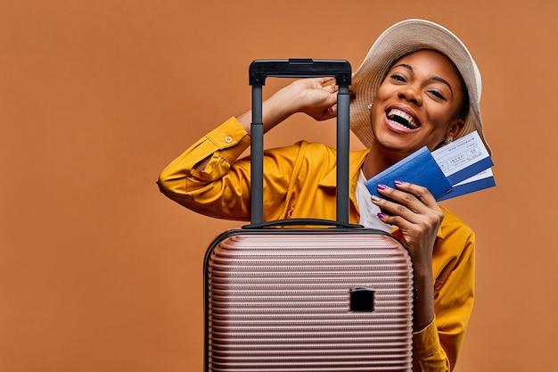 Donna con un cappello bianco in una giacca gialla con una valigia con un passaporto blu e due biglietti. concetto di viaggio