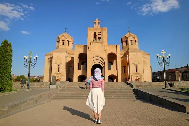 Donna in bianco copricapo di fronte alla cattedrale di yerevan, yerevan, armenia