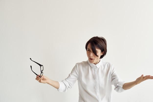 Donna in camicia bianca che tiene gli occhiali nell'ufficio professionale del manager delle mani