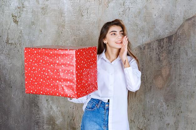 Donna in camicia bianca che tiene una confezione regalo rossa con puntini bianchi e chiama qualcuno per gestirla.