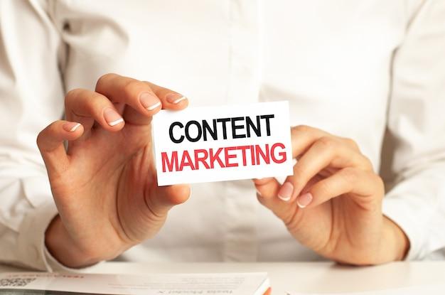 Una donna in camicia bianca tiene in mano un foglio di carta con il testo: content marketing. concetto di business per le aziende.