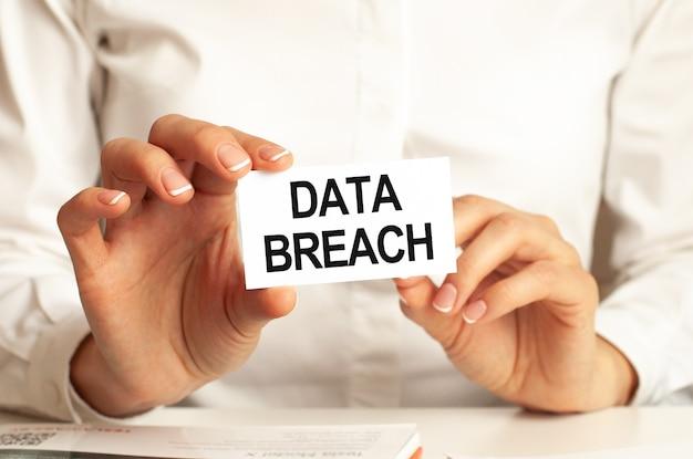 Una donna in camicia bianca tiene in mano un foglio di carta con il testo: data breach