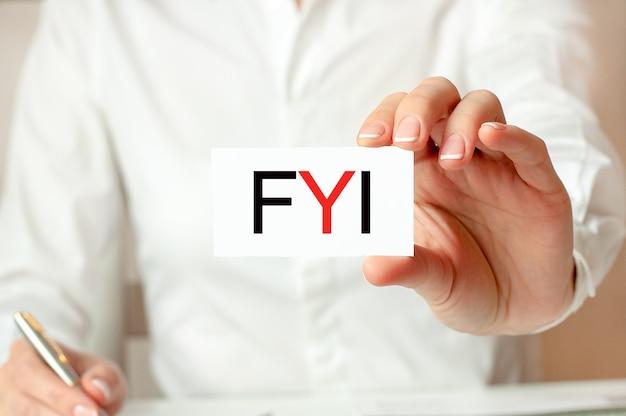 Una donna in camicia bianca tiene un pezzo di carta con il testo: fyi. cordiali saluti - per tua informazione. concetto di affari.