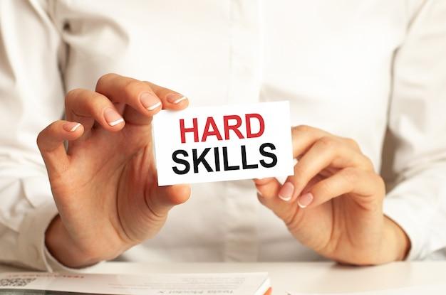 Una donna in camicia bianca tiene un pezzo di carta con il testo: hard skills. concetto di business per le aziende.