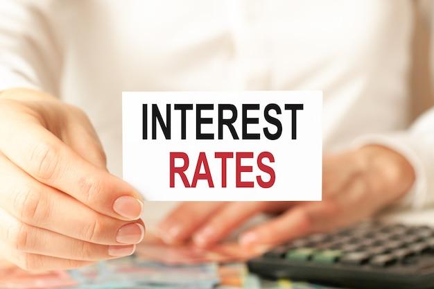 Una donna in camicia bianca tiene un pezzo di carta con il testo: tassi di interesse