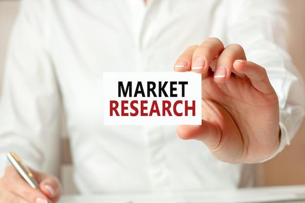 Una donna in camicia bianca tiene un pezzo di carta con il testo: ricerche di mercato. concetto di business per le aziende.