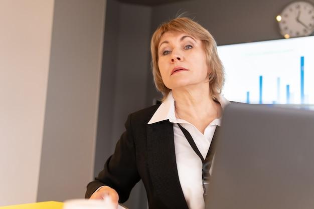 Una donna con una camicia bianca istruisce gli ascoltatori nella stanza degli affari.