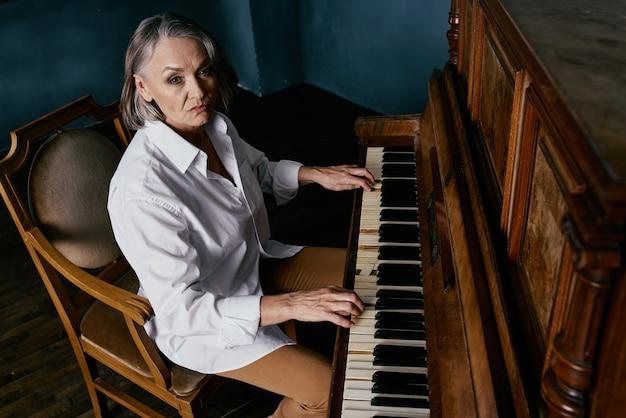 Una donna con una camicia bianca si siede su una sedia accanto a un pianoforte mentre impara la musica