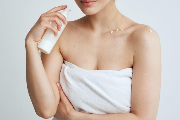 Donna in telo doccia bianco donne nude lozione per la pelle cura dermatologia. foto di alta qualità