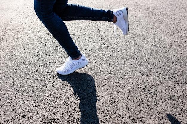 Donna in scarpe da ginnastica bianche in esecuzione su strada asfaltata al tramonto verso il sole, foto ravvicinata.