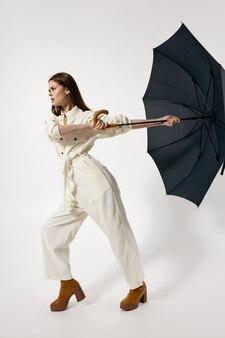 Donna in abito bianco che tiene un ombrello dal vento in stile moderno
