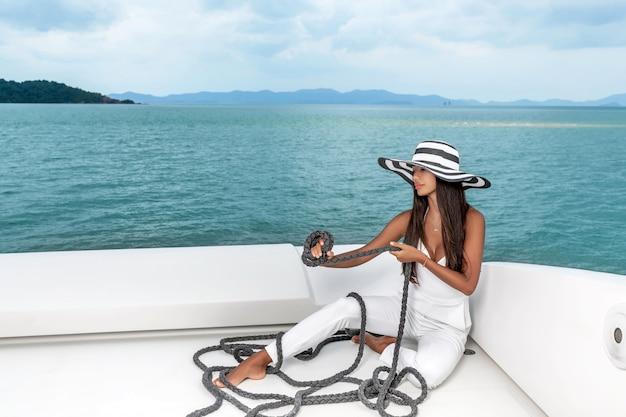 Donna in un abito estivo bianco e un cappello si siede sul ponte di uno yacht
