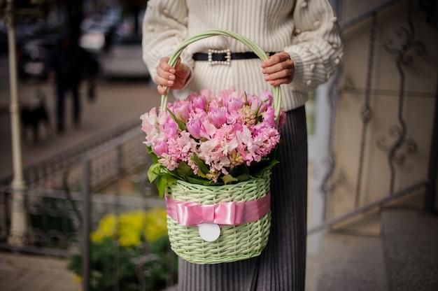 Donna in maglione bianco che tiene un bel cestino di vimini verde con fiori rosa