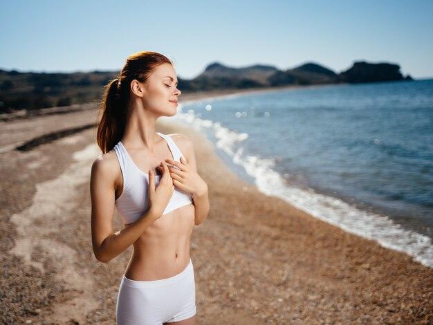 Donna in costume da bagno bianco sulla spiaggia oceano estate