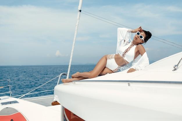 Donna in costume da bagno bianco in posa su uno yacht