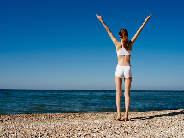 Donna in costume da bagno bianco esercizio yoga spiaggia lifestyle ocean