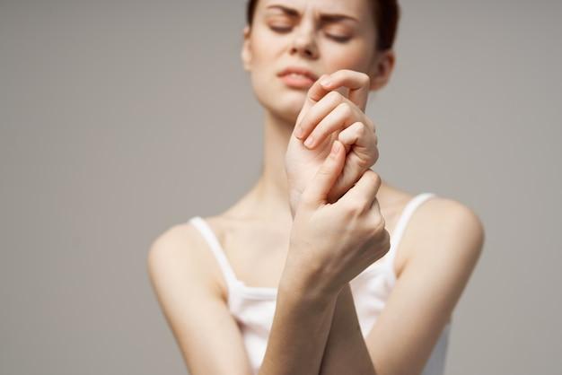 Donna in t-shirt bianca braccio dolore artrite malattia cronica sfondo chiaro. foto di alta qualità